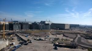 Bunkkeri oikealla. Betoniset ikkunattomat ulkoseinät. Sen vieressä vasemmalla, asuintalojen takaa, näkyy korkeampi harmaa Verkkokauppa.